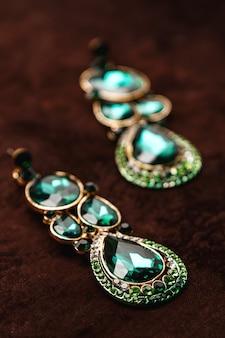 Brincos luxuosos com pedras verdes no veludo marrom