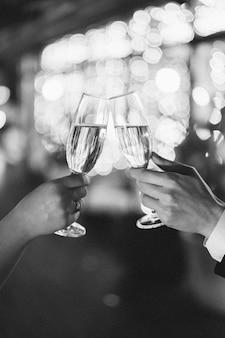 Brindando copos em um fundo desfocado. vista lateral preto e branco
