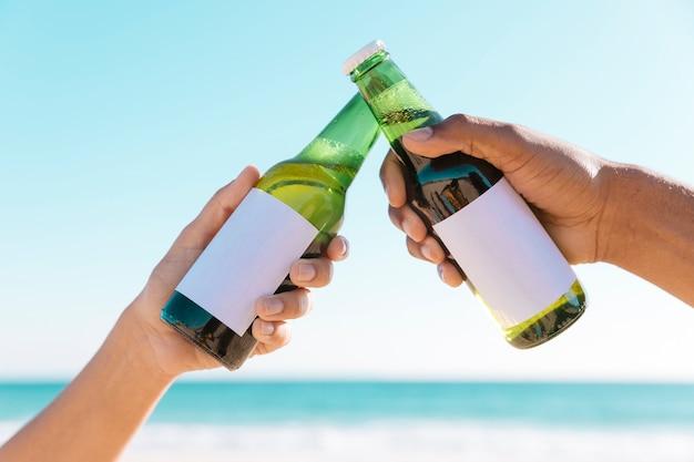 Brindar com duas garrafas perto do mar