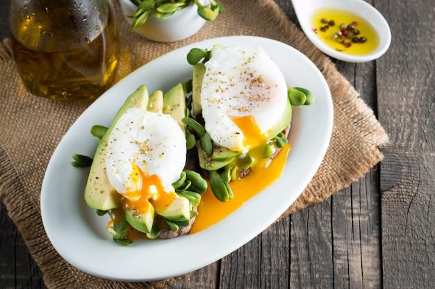 Brinde do abacate com o ovo do poacehd no fundo de madeira.
