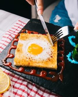Brinde do corte com ovo frito com cutelaria.