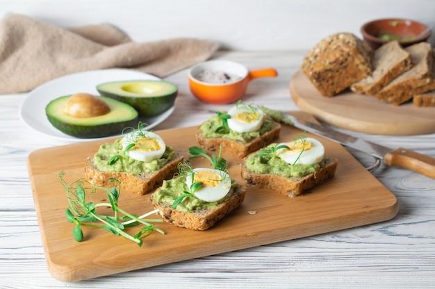 Brindes saudáveis com pão integral, abacate e ovo cozido na placa de madeira.
