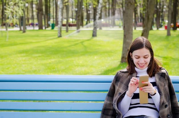 Brinette linda garota sentada num banco, sonhando e escrevendo seus planos em um notebook, relaxando em um parque em um dia ensolarado de primavera
