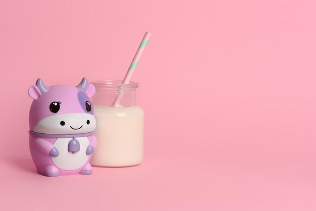 Brinque a vaca com um copo de leite em um fundo rosa. copie o espaço.