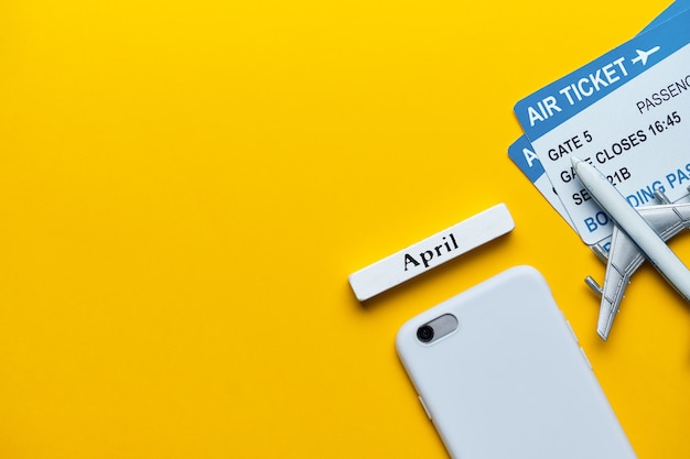 Brinque o avião em um fundo amarelo como um conceito do feriado de abril da mola com espaço da cópia.
