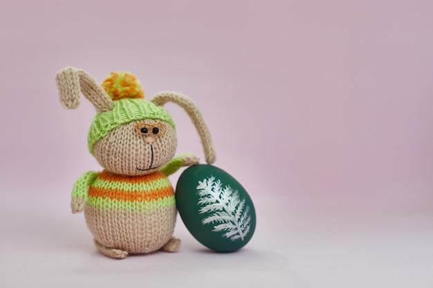 Brinque o coelhinho da páscoa com ovo colorido em um fundo rosa.
