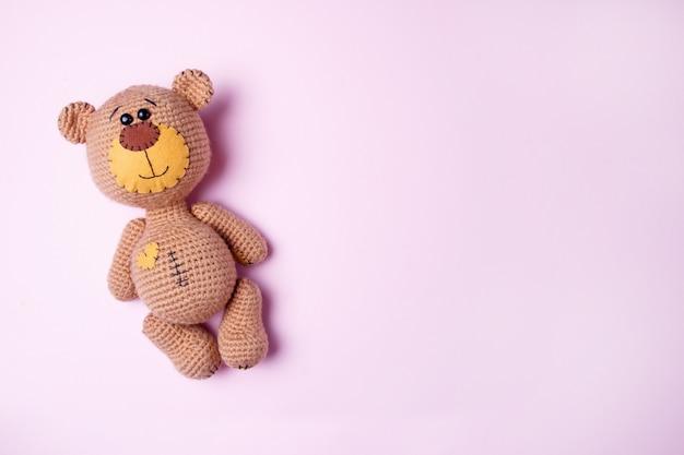 Brinque o urso de peluche isolado em um fundo rosa. fundo de bebê. copie o espaço, vista superior.