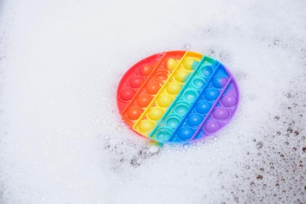 Brinquedo antiestresse com bolhas de silicone estourá-lo em espuma com sabão no espaço de cópia do banheiro