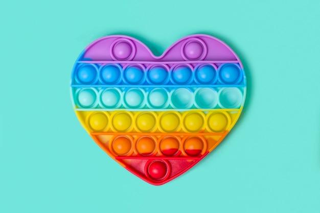 Brinquedo antistress pop it de silicone colorido e elegante na forma de um coração de arco-íris