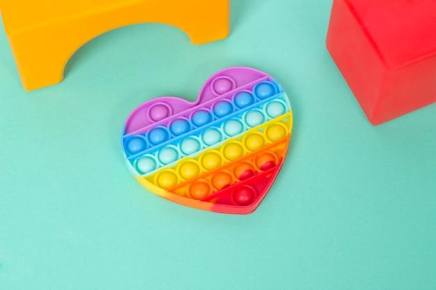 Brinquedo antistress pop it de silicone colorido em forma de coração de arco-íris sobre fundo de menta pastel