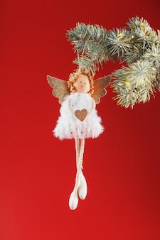 Brinquedo artesanal de anjo de natal em uma árvore de natal