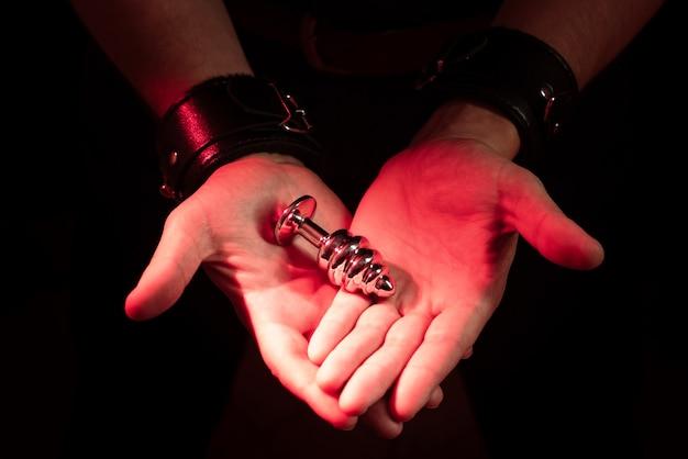 Brinquedo bdsm. plug anal nas palmas das mãos dos homens