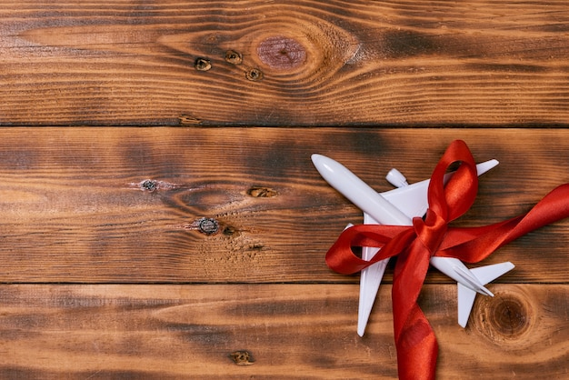 Brinquedo branco em branco de avião de passageiros com ribbin em fundo de madeira rústico. celebração de natal e ano novo