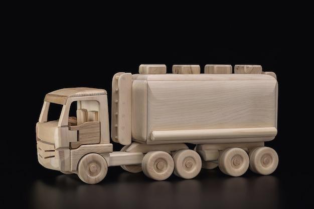 Brinquedo, caminhão de madeira com tanque, carro com tanque para transporte de gás, óleo. fundo escuro, cópia espaço, estúdio tiro.