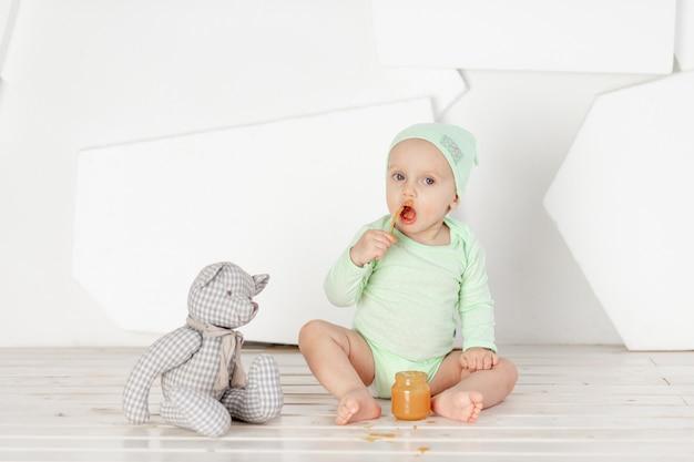 Brinquedo colher de alimentação de bebê em body verde, conceito de alimentação e comida para bebê