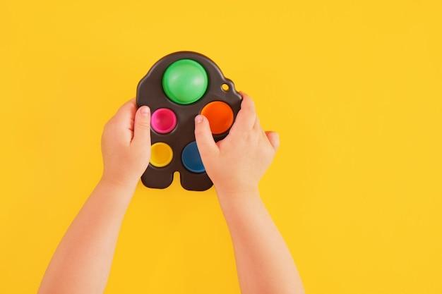 Brinquedo colorido covinha simples nas mãos da criança sobre fundo amarelo, brinquedo sensorial para o desenvolvimento das habilidades motoras finas das mãos