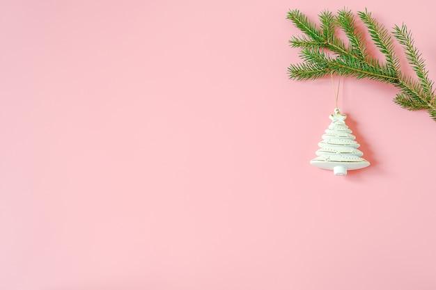 Brinquedo da árvore da decoração do white christmas no ramo do abeto no fundo cor-de-rosa. feliz natal ou feliz ano novo.