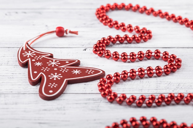 Brinquedo de árvore de natal vermelho e festão em madeira branca