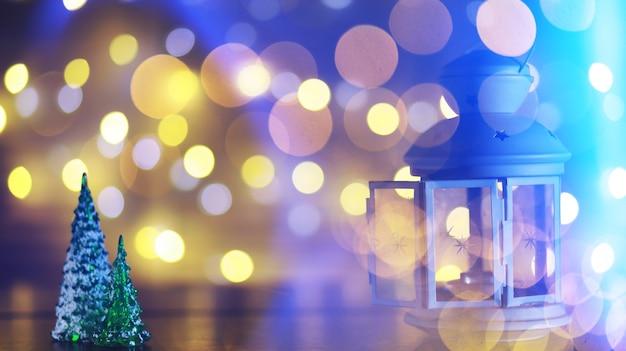 Brinquedo de árvore de natal vermelho em um galho de uma árvore de abeto natural com luzes de guirlandas desfocadas no fundo. brinquedo de metal com fendas de veado e flocos de neve. natal, ano novo, cópia espaço, bokeh.
