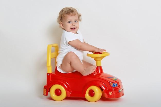 Brinquedo de bebê animado sentado em um tolocar vermelho e amarelo e olhando para a câmera com uma expressão facial satisfeita, vestindo macacão