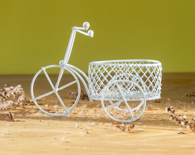 Brinquedo de bicicleta de três rodas retro branco com cesta na mesa de madeira em vibrações de verão de parede amarela com choupo ...