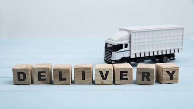 Brinquedo de caminhão de entrega e cubos quadrados em fundo azul
