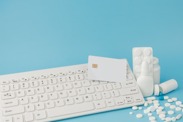 Brinquedo de carrinho de compras com medicamentos e teclado. comprimidos, blister, frascos médicos, termômetro, máscara protetora sobre um fundo azul.