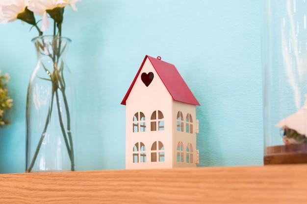 Brinquedo de casa pequena com forma de coração na decoração de prateleira de madeira