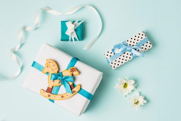 Brinquedo de cavalo de balanço com caixas de presente; flores e fita sobre o pano de fundo azul