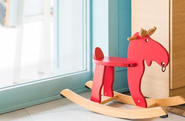 Brinquedo de cavalo de balanço vermelho para criança na sala de estar em casa, alegre montando coisas criança mobília de fundo