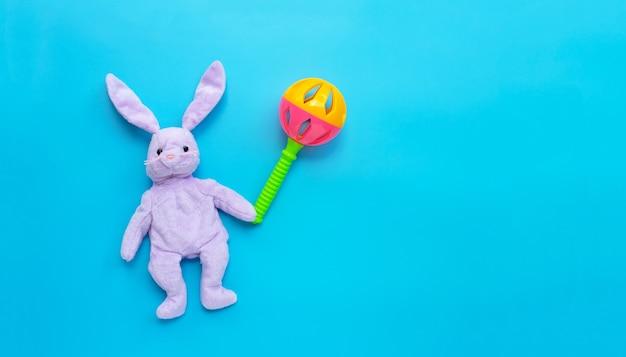 Brinquedo de coelho com chocalho de bebê colorido sobre fundo azul. copie o espaço