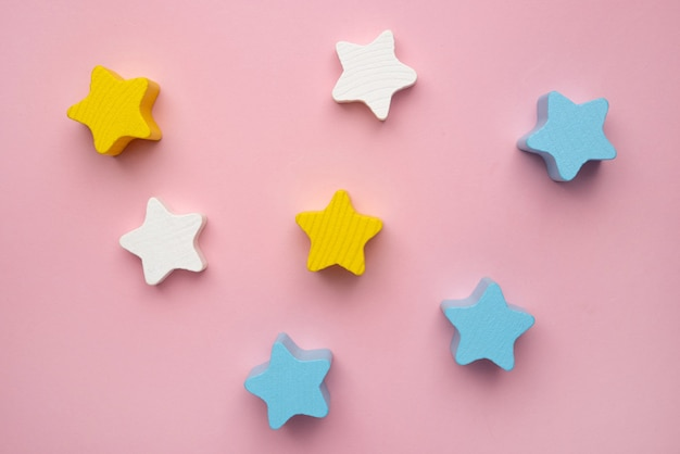 Brinquedo de desenvolvimento infantil para o desenvolvimento de habilidades motoras - um balanceador de estrelas de madeira em forma de lua crescente em um fundo rosa
