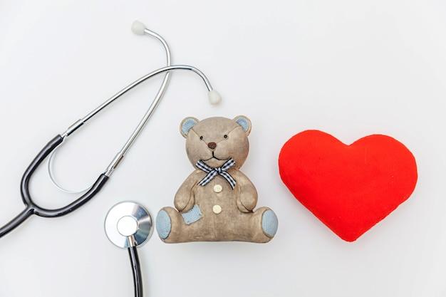 Brinquedo de design minimalista com coração vermelho e estetoscópio de equipamentos de medicina isolado no fundo branco