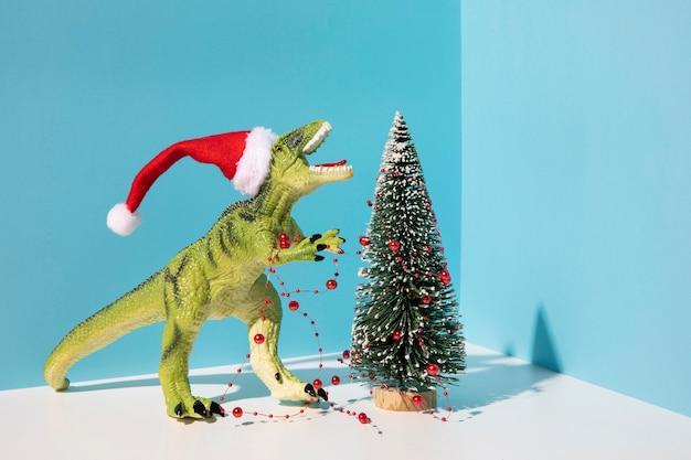 Brinquedo de dinossauro perto da árvore de natal