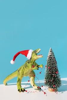 Brinquedo de dinossauro perto de árvore de natal decorada
