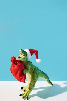 Brinquedo de dinossauro segurando um saco vermelho