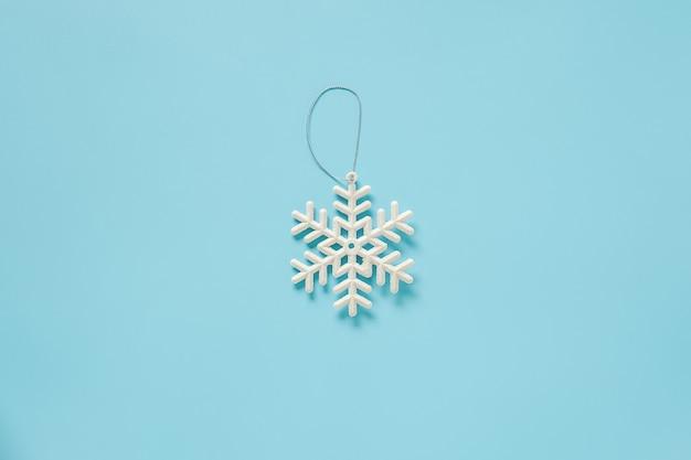 Brinquedo de floco de neve de decoração de natal branco sobre fundo azul, com espaço de cópia