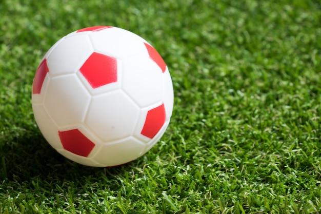 Brinquedo de futebol de cor vermelho e branco em fundo de relva artificial