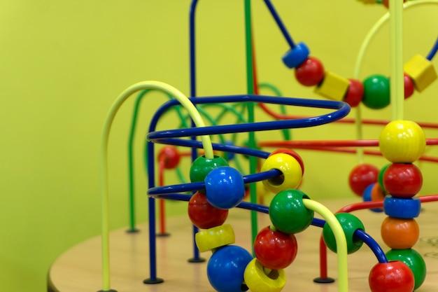 Brinquedo de lógica educacional de madeira com caminhos no bebê da criança na sala do berçário