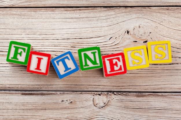 Brinquedo de madeira blocos com o texto: fitness