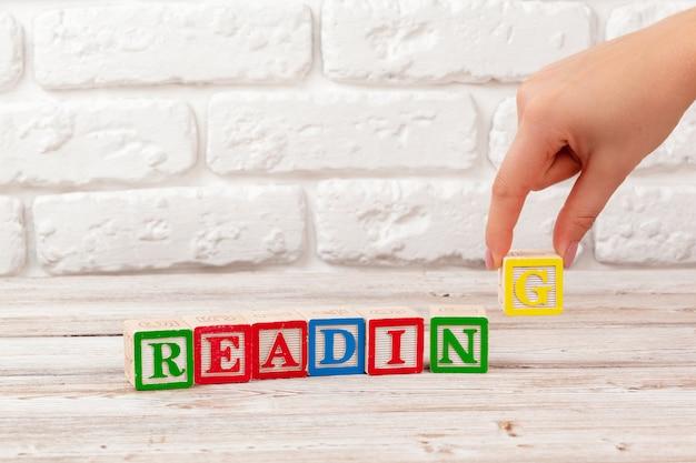 Brinquedo de madeira blocos com o texto: leitura