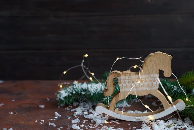 Brinquedo de madeira cavalo de balanço como de decorações de ano novo com neve e fer árvore