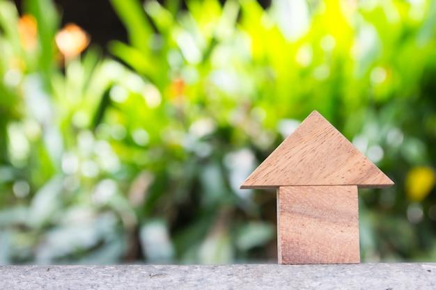 Brinquedo de madeira como o conceito de casa de sonho com blackground verde turva