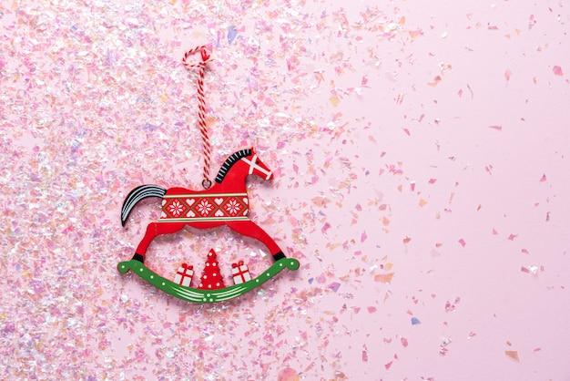 Brinquedo de madeira da árvore de natal do cavalo de balanço no rosa com glitter. vista plana leiga, superior com copyspace