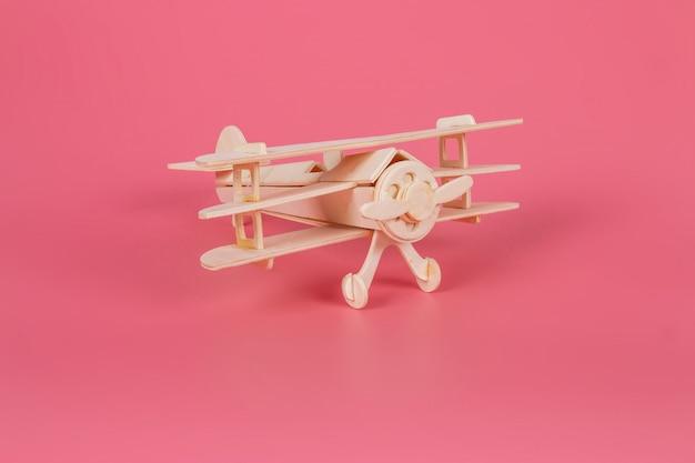 Brinquedo de madeira do avião em um fundo rosa pastel