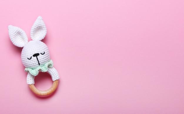 Brinquedo de madeira eco bebê, coelho de saco de feijão em fundos rosa com espaço de cópia. vista superior, plana leiga.