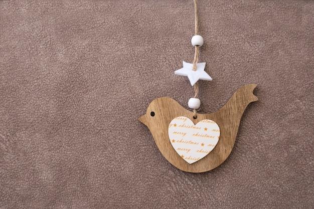 Brinquedo de madeira para a árvore de natal em forma de um pássaro em um fundo marrom