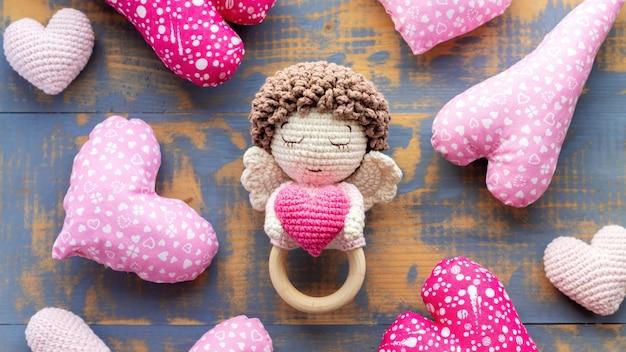 Brinquedo de malha artesanal para crianças e um coração rosa. vista do topo