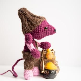 Brinquedo de malha artesanal. um rato de malha com uma motocicleta amarela