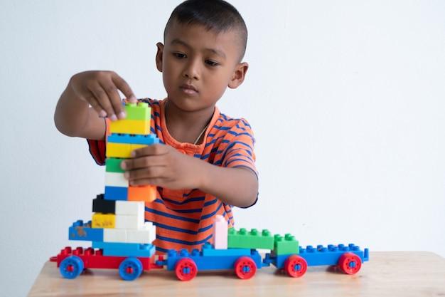 Brinquedo de menino asiático bonito jogar na sala